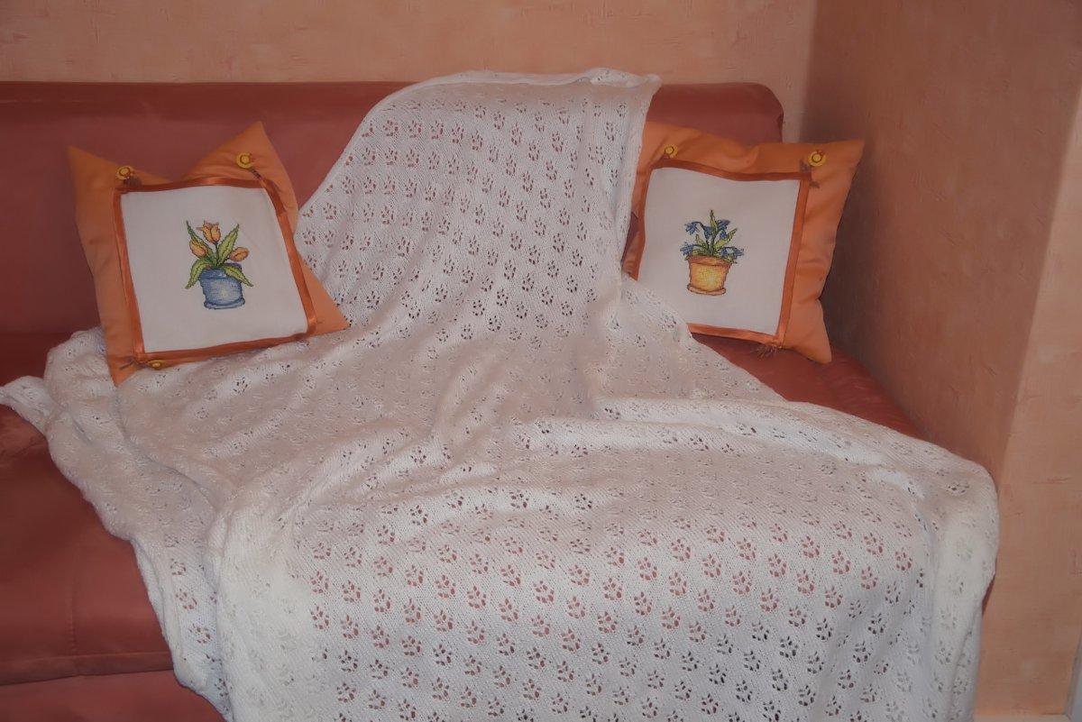 Plaid mit zwei farblich passenden Kissen auf Sofa